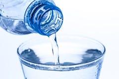 A água de derramamento em uma água de vidro elegante deixa cair no fundo branco Fotografia de Stock Royalty Free