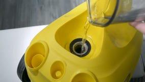 A água de derramamento no dispositivo do líquido de limpeza do vapor antes de usá-lo entrega a close up a vista superior filme