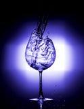 Água de derramamento no vidro de vinho com equilíbrio branco azul do fundo preto Foto de Stock