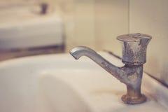 Água de desperdício, torneira de água no toalete público sujo Imagem de Stock