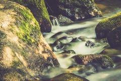 Água de fluxo através das pedras fotografia de stock royalty free