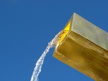 Água de fluxo da fonte dourada fotografia de stock