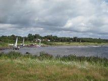 A água de Halmstad da Suécia abriga o cinza da grama de nuvem do verão dos barcos de navigação fotos de stock