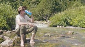 Água de mola bebendo do homem do caminhante da garrafa na costa do rio na floresta da montanha filme