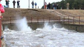 Água de observação dos povos que raging na represa durante a inundação da mola Rio da inundação durante o derretimento da neve video estoque