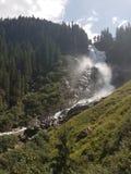 Água de pressa de Áustria da cachoeira de Krimml com poder extremo cercada por árvores verdes altas e pelo céu brilhante azul fotografia de stock royalty free