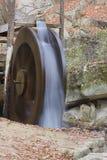 A água de queda faz o waterwheel girar imagens de stock