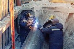 Água de solda do soldador ou encanamento de aço do gás com o trabalhador assistente na trincheira Renovação e replacemen subterrâ imagens de stock royalty free