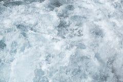 Água de superfície de mar áspero, superfície azul da água da textura da espuma da onda do mar atrás do barco de motor movente ráp foto de stock