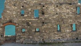 A água de turquesa do golfo dos poetas aparece entre as ruínas das paredes antigas do centro histórico de Portovenere, Ligur fotografia de stock