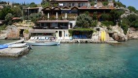 A água de turquesa perto da praia e restaurantes exteriores em Kekova video estoque
