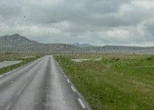 A água deixa cair na janela de carro após a chuva com a estrada só entre montanhas e geleira em um fundo, Islândia sul, Europa imagens de stock royalty free