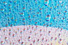 A água deixa cair nos meios do dvd, gotas da água no fundo colorido fotos de stock royalty free