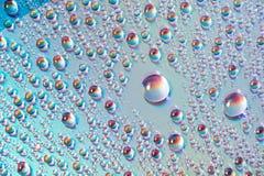 A água deixa cair nos meios do dvd, gotas da água no fundo colorido fotos de stock