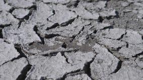A água deixa cair a queda no solo fraturado seco da seca filme