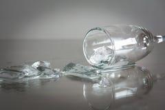 Água derramada com os cubos de gelo na tabela Vidro com água derramada Fotografia de Stock Royalty Free