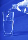 A água derramou dentro um vidro Imagem de Stock Royalty Free