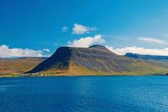 Água do mar azul na paisagem da montanha no isafjordur, Islândia Litoral montanhoso no céu azul ensolarado Férias de verão sobre imagem de stock
