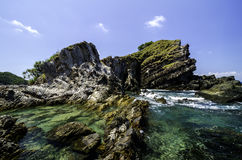 A água do mar clara cercou a ilha rochosa com fundo do céu azul no dia ensolarado Foto de Stock