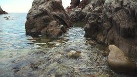 A água do mar clara está espirrando em pedras grandes na costa, opinião do close-up vídeos de arquivo