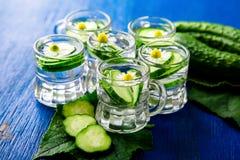 Água do pepino em seis frascos de vidro do pedreiro pequeno no fundo azul rustic detox Imagem de Stock Royalty Free