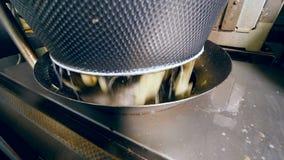 A água e as batatas estão caindo em uma máquina industrial filme