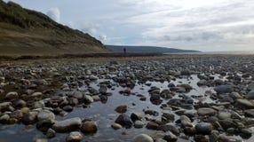 Água e pedras sob um céu nebuloso em uma praia na Irlanda Imagens de Stock Royalty Free