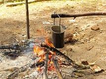 A água em um potenciômetro de acampamento ferve sobre um fogo em um acampamento da floresta no verão imagem de stock