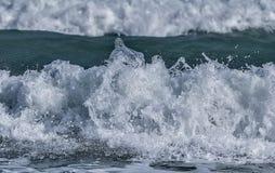 A água espirra na crista de onda do mar/oceano contra o CCB borrado Fotos de Stock Royalty Free