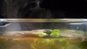Água a ferver com o vapor, cozinhando vegetais na bandeja de vidro vídeos de arquivo