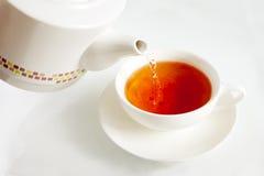 Água a ferver de derramamento em um copo de chá fotos de stock