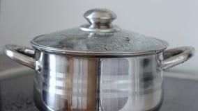 Água a ferver em uma caçarola com tampa de vidro, close up A água gorgoleja, polvilha e flui da bandeja filme