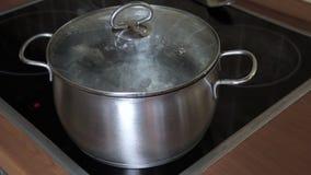 Água a ferver na bandeja com uma tampa fechado em uma parte superior moderna cerâmica do cozinheiro do fogão do vidro da indução vídeos de arquivo
