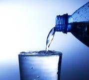 Água fresca de derramamento em um vidro fotos de stock