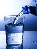 Água fresca de derramamento em um vidro foto de stock royalty free