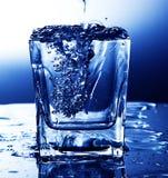 Água fresca de derramamento em um vidro imagens de stock royalty free