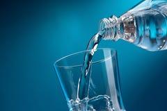 Água fresca de derramamento em um vidro Fotografia de Stock Royalty Free