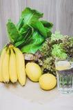 Água fresca do limão com limões, as bananas e salada amarelos das plantas verdes Dieta, conceito saudável, ainda vida Casa feita Imagens de Stock