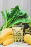 Água fresca do limão com limões, as bananas e salada amarelos das plantas verdes Dieta, conceito saudável, ainda vida Casa feita Imagem de Stock