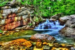 Água fresca que conecta sobre grandes rochas em um córrego pequeno HDR Fotografia de Stock