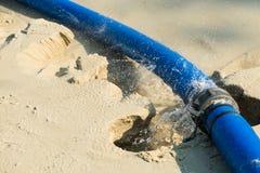 Água fresca que escapa na junção de borracha azul do ` s da mangueira na praia da areia Fotos de Stock