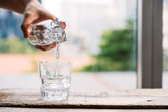 Água fresca refinada de derramamento da bebida da garrafa na tabela em l fotos de stock royalty free