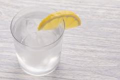 Água fria de refrescamento com limão Com gelo pronto para comer Está em seguida uma faca após ter cortado o fruto Vidro de Misted imagem de stock royalty free