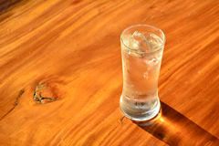 Água fria na tabela de madeira sobre fundida posta de vidro Imagem de Stock