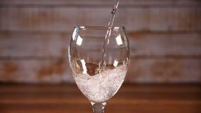 Água gasosa mineral que flui no vidro transparente - movimento lento filme