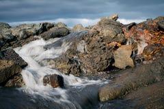Água glacial que corre através de pedras da lava foto de stock