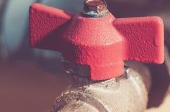 ?gua/guindaste vermelhos abertos da v?lvula com a porta para a ?gua toned foto de stock
