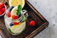 Água infundida da desintoxicação com fatia, framboesa, mirtilo e hortelã do limão Cocktail gelado ou limonada do verão no frasco  Fotografia de Stock