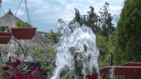 A água lenta sai da fonte no pátio video estoque
