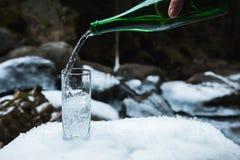 A água mineral mineral é derramada de uma garrafa verde de vidro em uma taça de vidro clara Imagens de Stock Royalty Free